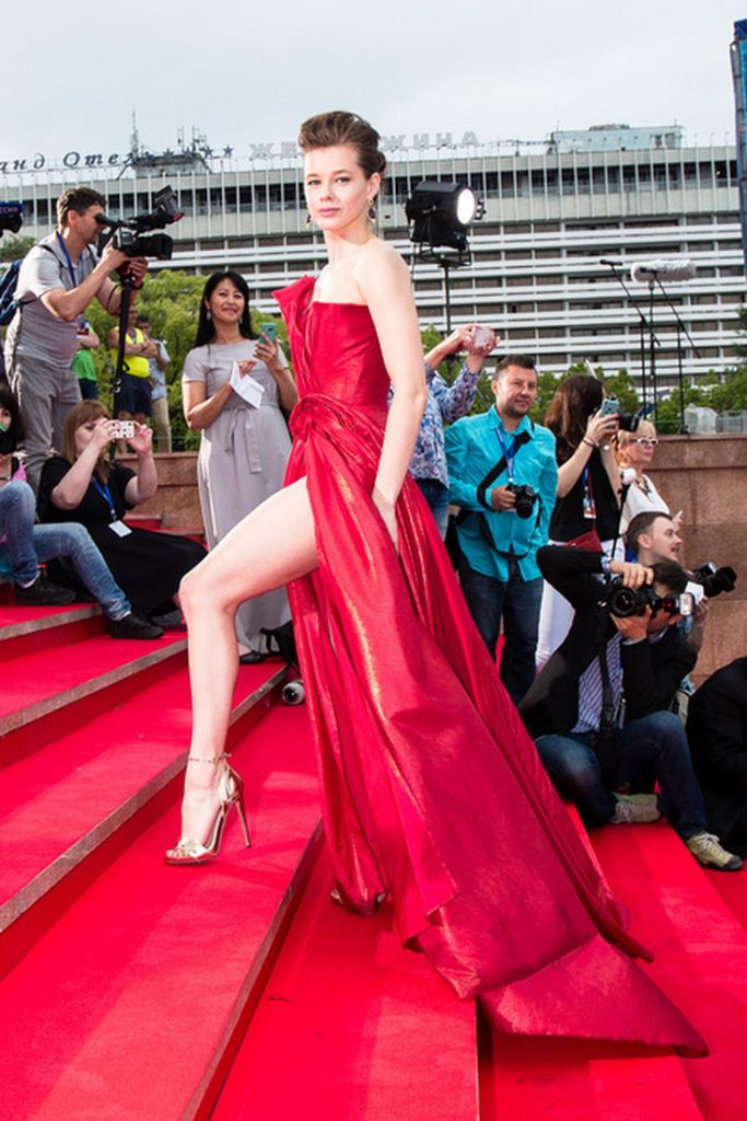 Екатерина Шпица в ярко-красном платье-бюстье в пол пышного кроя с драпировкой на груди и высоким разрезом подола